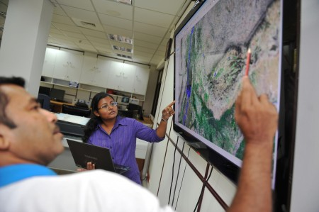 GIS staff discuss a satellite map.