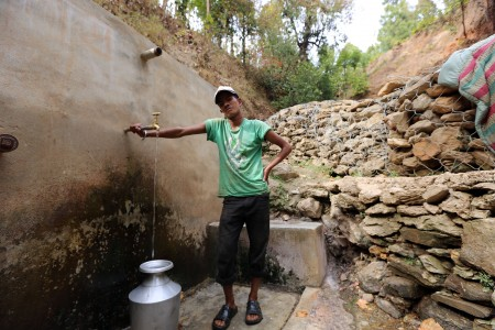A young man collects water from a spring in Nepal.