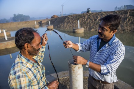 A scientist measuring the water collected from a pond created under the Underground Taming of Floods for irrigation