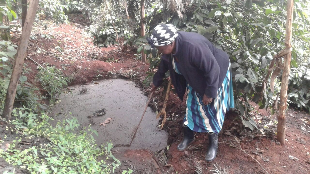 Dionesia Ireri, a coffee farmer in Kenya, stirs the cow dung mixture that she transforms into biogas with the help of a biodigester.