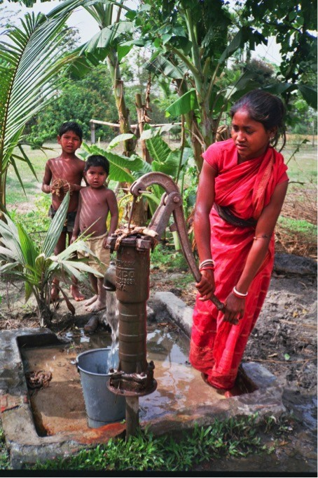 A woman beneficiary of a hand pump in 1995.