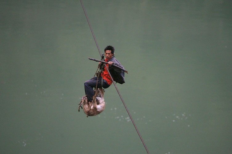A man and his goat cross over the Nu River on a cable, near Lushui southwest China's Yunnan province.