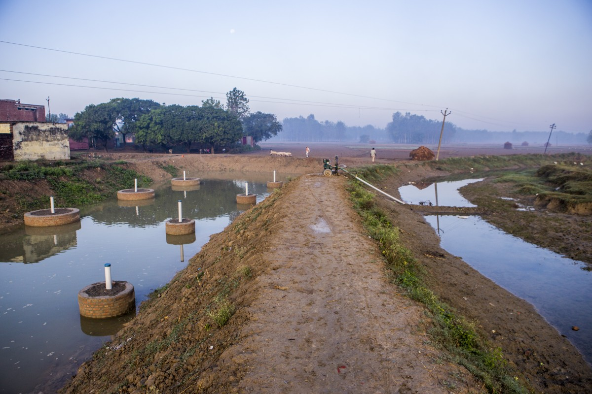 A view of a stream and water collected pond created under the Underground Taming of Floods for irrigation (UTFI)