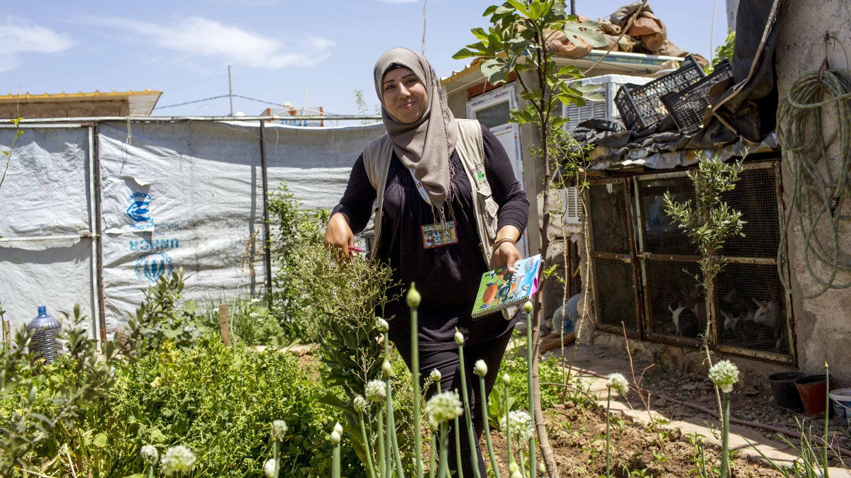 Syrian refugee and local community outreach officer from the NGO Lemon Tree Trust visiting a home garden in Domiz Refugee Camp, Iraq.