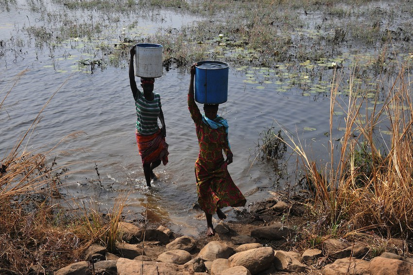 Women collect water in west Africa
