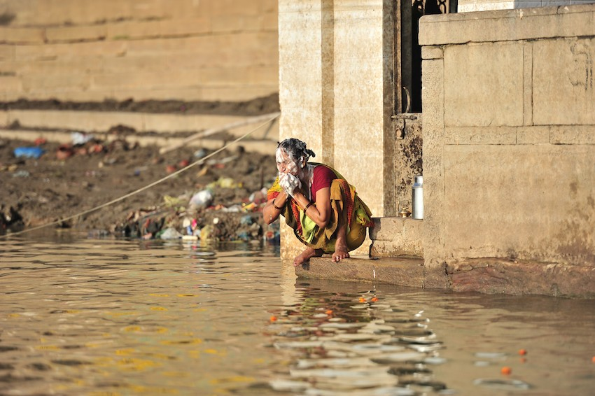 Woman washes her face in the river Ganga