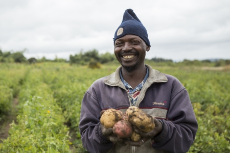A farmer showing potatoes he has grown in a village near Iringa, Tanzania.