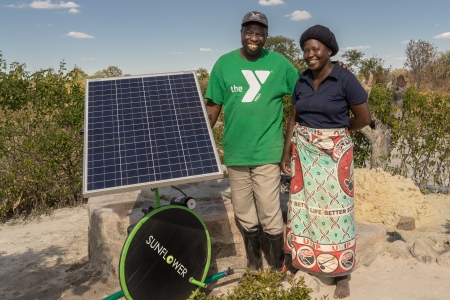 Kenyan farmers posing with a solar irrigation pump.