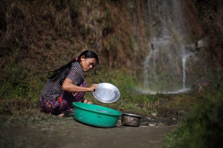 A woman uses water from a spring for daily needs.