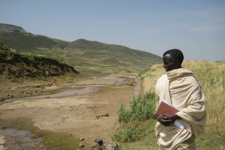 A man looks onto a dried out stream during a drought in Ethiopia.