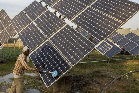 Farm workers clean the solar panels of a solar water pump at the farms of Gurinder Singh.