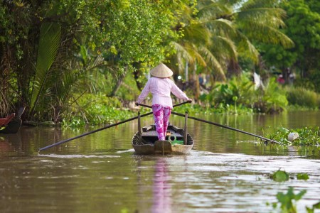 Woman steering a boat down a canal off the Hau River in Can Tho Province, Vietnam.