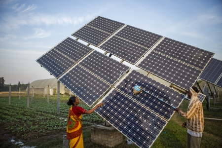 Farm workers clean the solar panels for better efficiency
