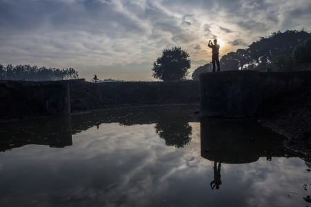 A scientist tests the water collected from a pond created under the Underground Taming of Floods for irrigation (UTFI) initiative.