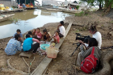 Douglas Varchol films while women clean fish. Tonle Sap, Cambodia.