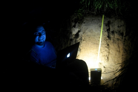 Daniel Hirmas, a professor at University of Kansas, uses the MLT scanner at night in a soil pit.