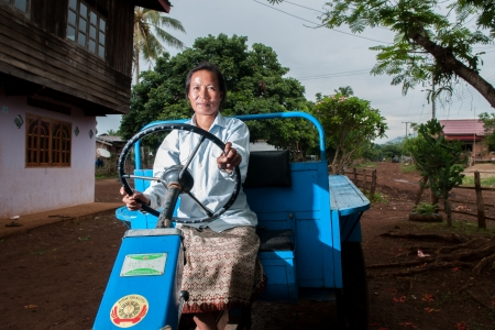 A female farmer demonstrating the tractor she bought with funds from cassava.