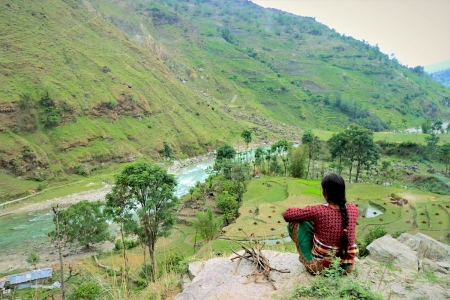 Woman looking over river valley, in Nepal